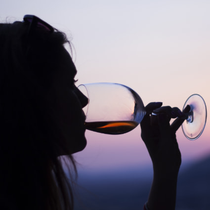 A silhouetted woman sips wine at sunset