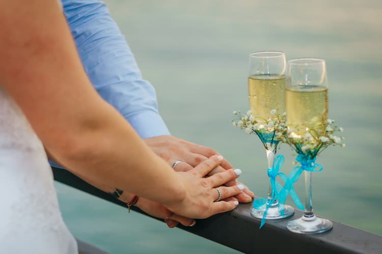 A couple holding hands besides two glasses of champagne