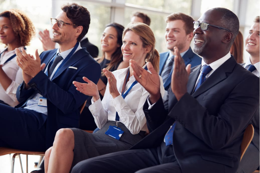 audience members clapping during a seminar