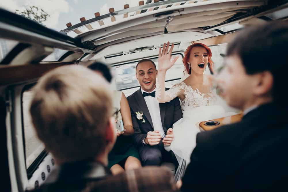 Red-haired bride and dark-haired groom in back of limo with friends