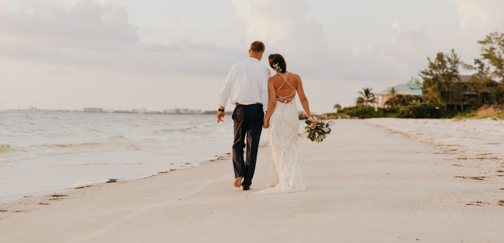 a happy bride and groom walk down the beach holding hands