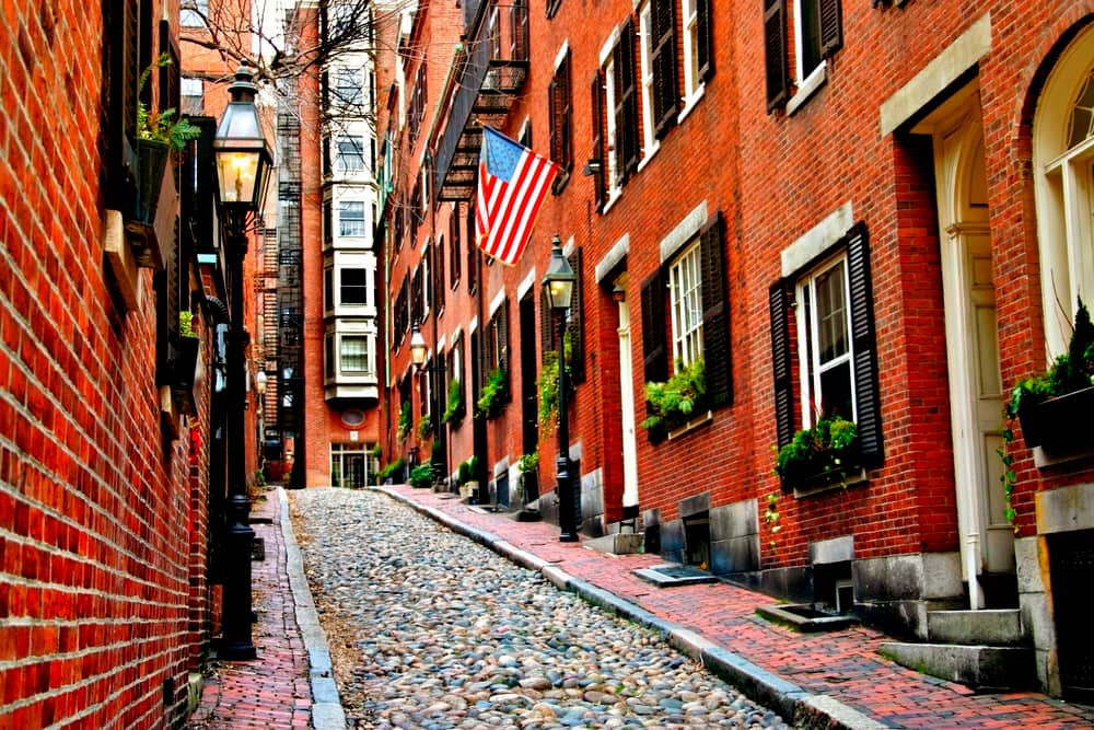 a cobblestone street with old townhomes in boston's beacon hill neighborhood