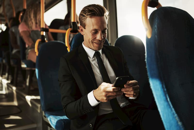 professional man in suit riding on charter bus looking at phone and smiling