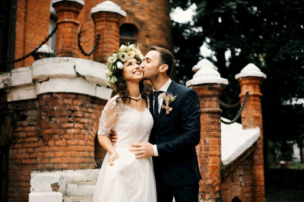 a groom kisses a bride on the cheek at a boston wedding venue