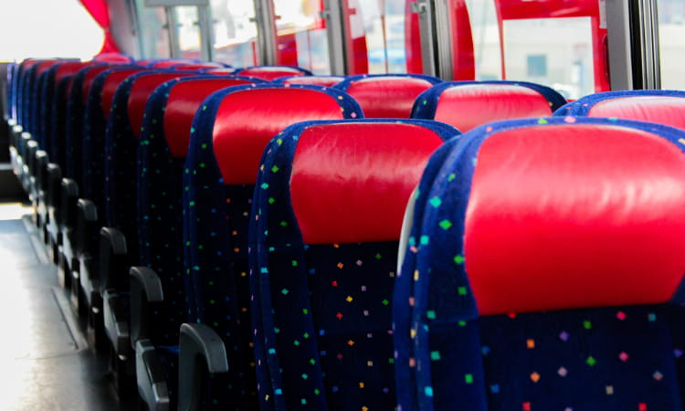 rows of seats inside an empty charter bus, all blue with red headrests