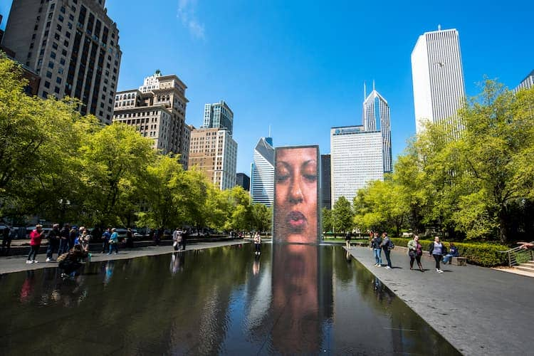 a screen with a woman's face over a reflecting pool at millennium park