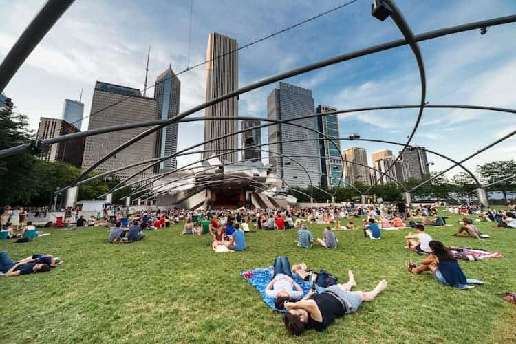 visitors lay in the grass at chicago's millennium park