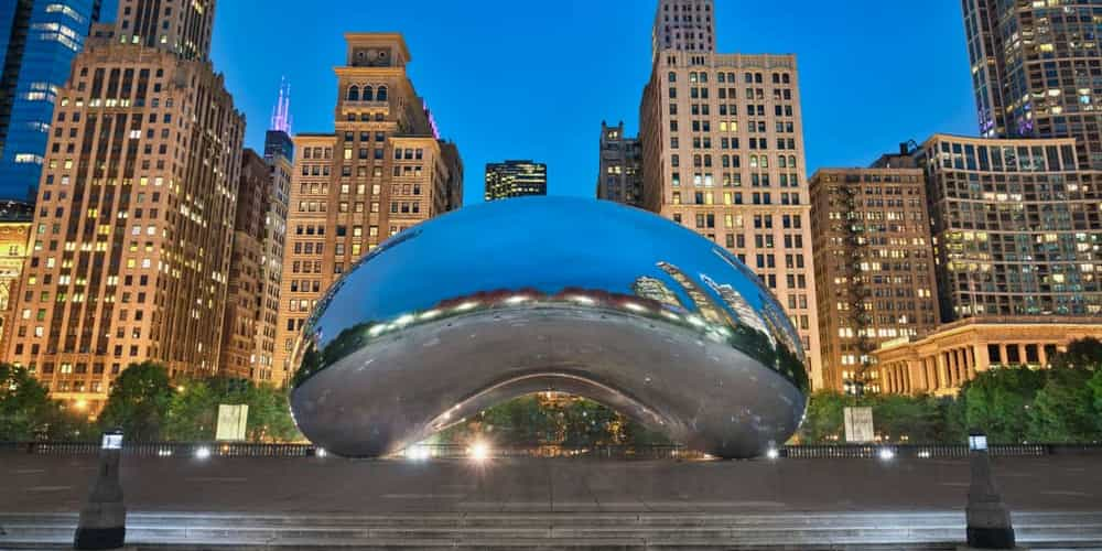 the reflective cloud gate in chicago's millennium park with a cityscape in the background
