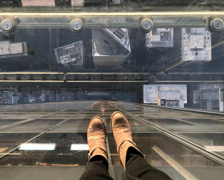 a view of a guest's feet as they stand atop Willis Tower and look toward the street