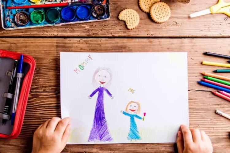 Child drawing picture of her and her mother