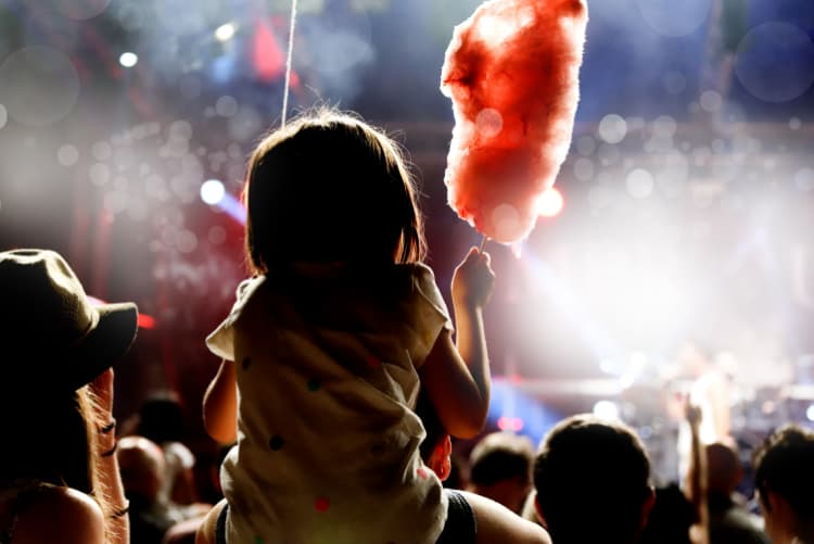 A silhouette of a child watching a concert