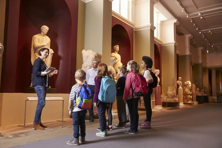 A group of children staring at a sculpture in a museum