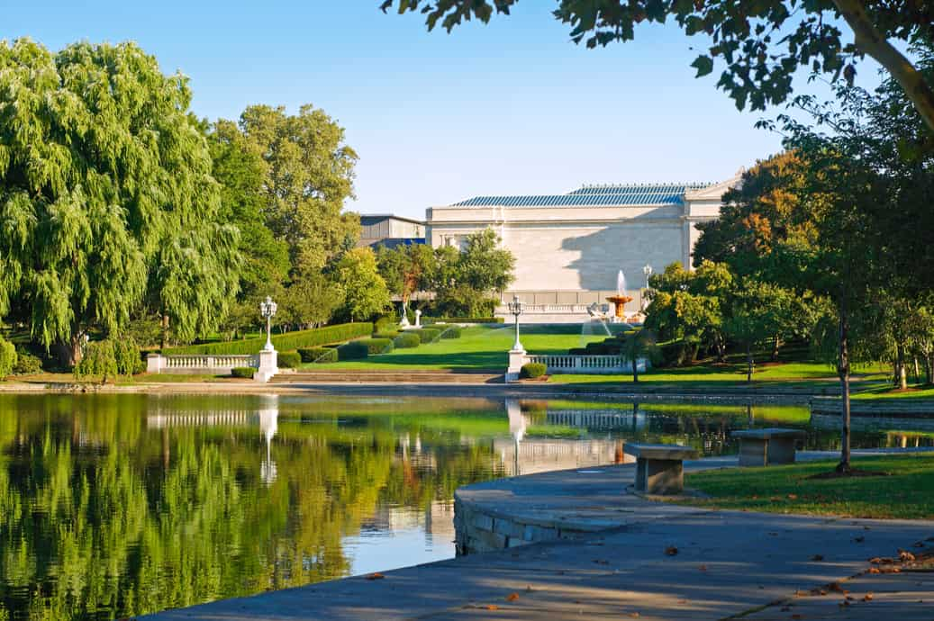 the exterior of the cleveland museum of art, with green grass and a pond