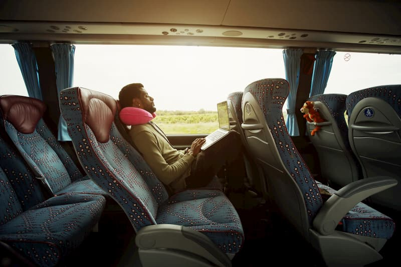 portrait of man relaxing on charter bus with computer on lap