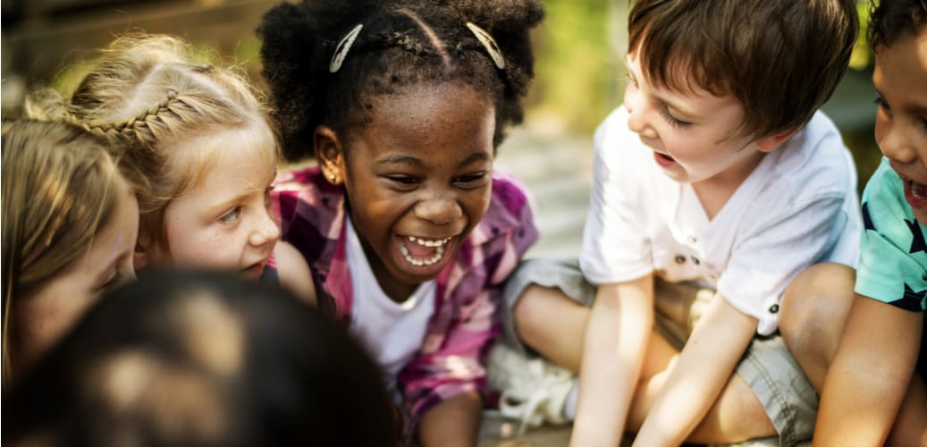 kids smile and laugh together while they're outside on a field trip