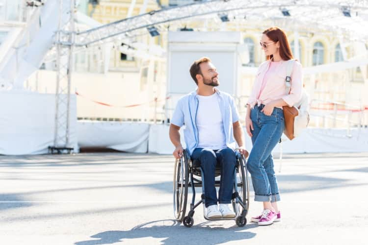 A man in a wheelchair and a woman enjoying a theme park