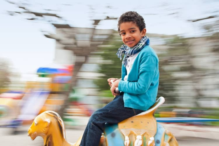 A young child smiling on a theme park ride