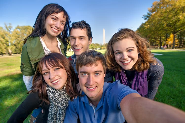 friends pose and smile in front of the washington monument