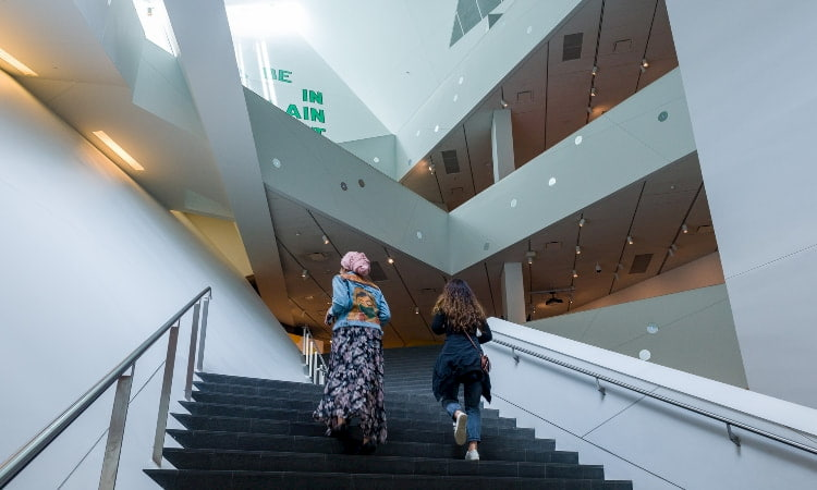 two women walk up the stairs in the main atrium of the denver art museum