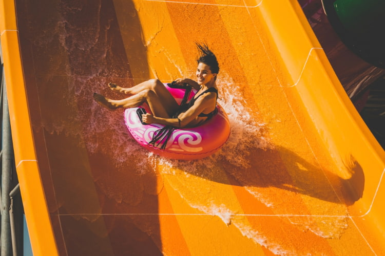 a girl plunges down a waterslide in a tube at Elitch Gardens in Denver