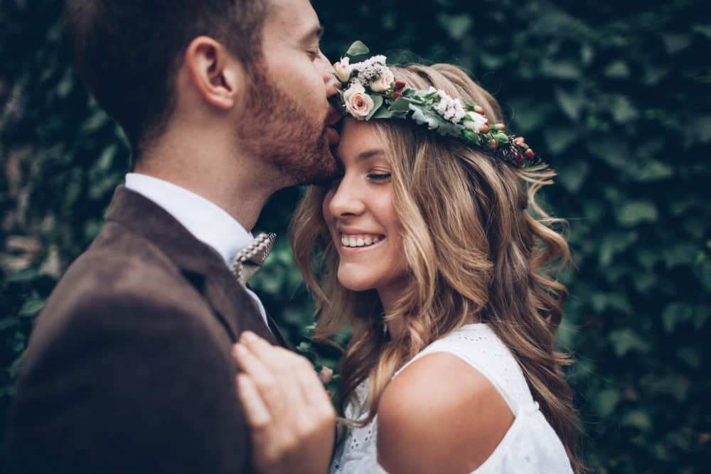 Bride and groom embracing and smiling with flowers