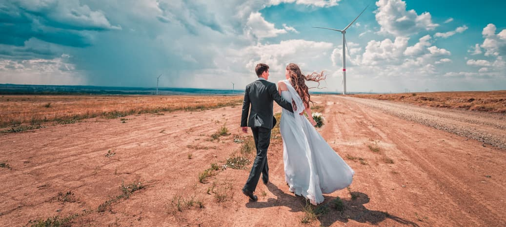 a bride and groom embrace and walk through the desert