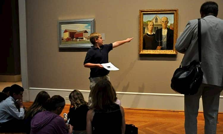 Student pointing at painting during presentation at Art Institute