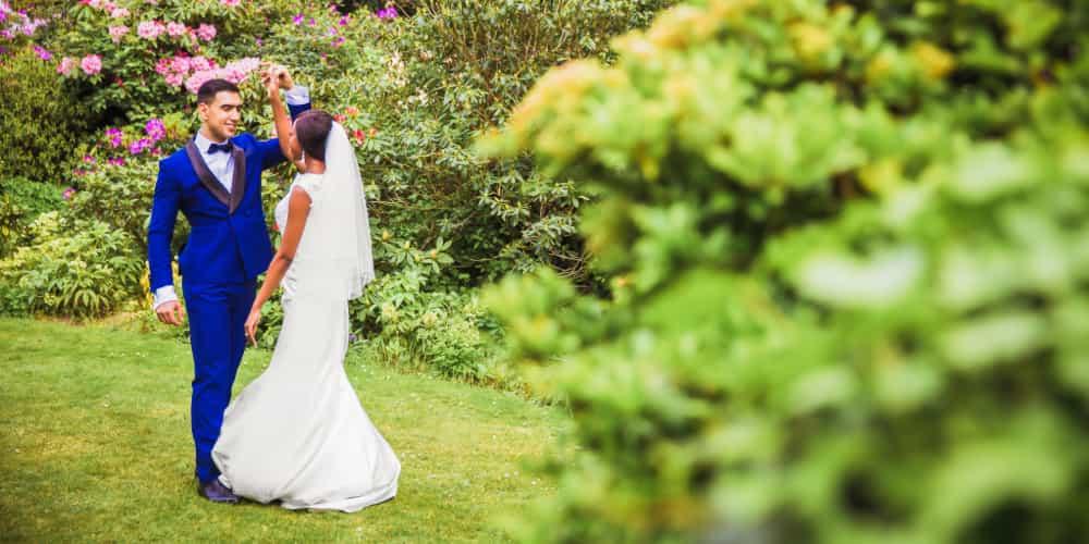A happy wedding couple dances in a flower garden