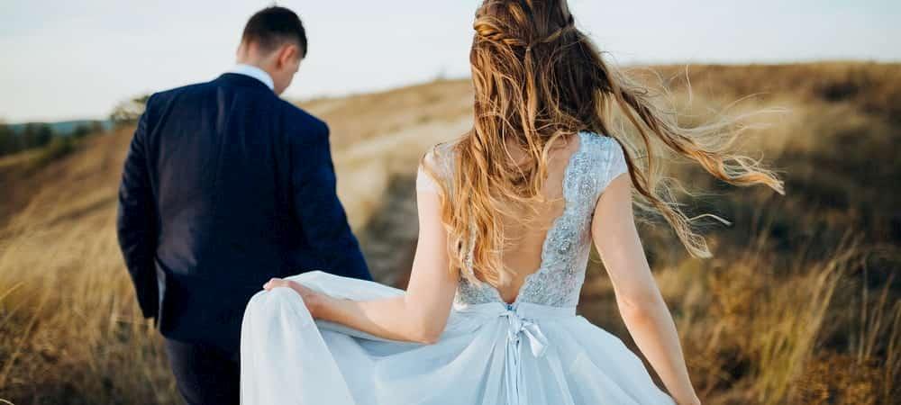 a couple walk through a field on their wedding day
