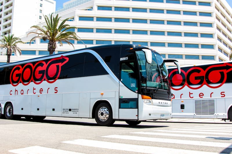 a white charter bus with a gogo charters logo parked outside of a large building
