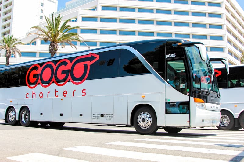 a white charter bus with the 'gogo charters' logo parked outside of a large building