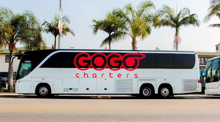 A GOGO charter bus parked by trees