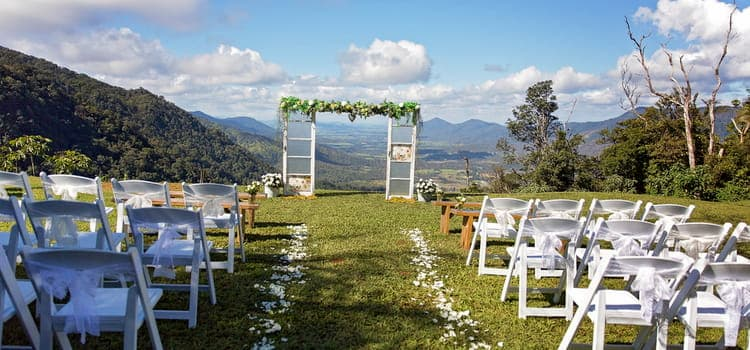 an altar and seats sit ready for a wedding ceremony with the mountains in the background
