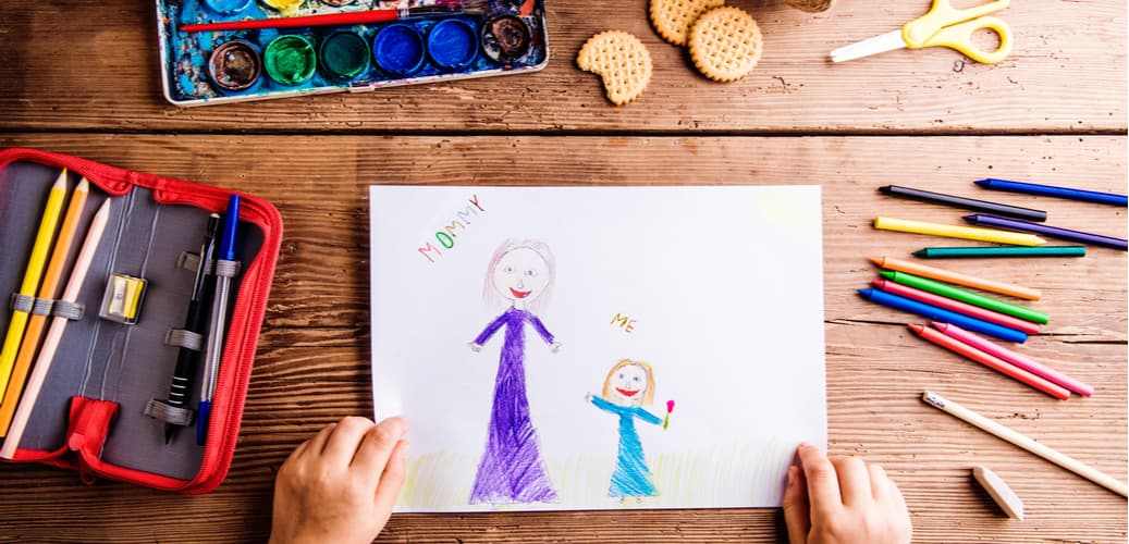 child-drawing-a-picture-with-stationary-on-table