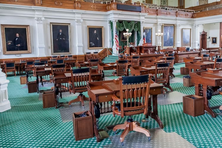 a gathering space inside the texas state capitol, with wooden chairs and green carpet