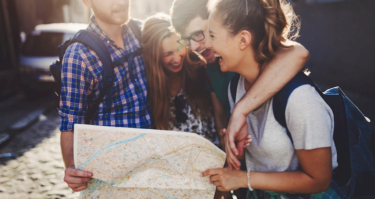friends laugh with a map as they explore Los Angeles
