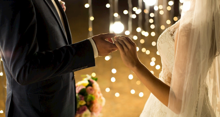 bride and groom hold hands in front of glittering lights