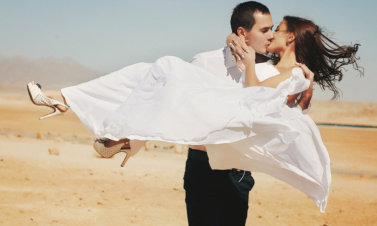 a groom carries a bride through the desert as they kiss
