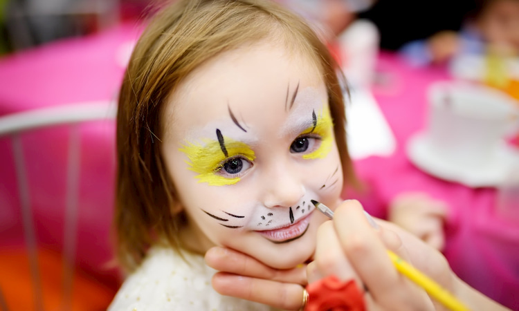 a child has her face painted in a tiger design at a San Diego Zoo party