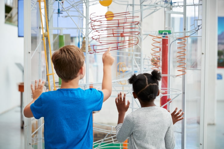two children stand in awe at a museum exhibit