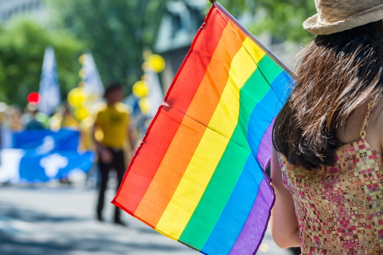 a woman with a rainbow flag watches the San Francisco Pride Parade pass by