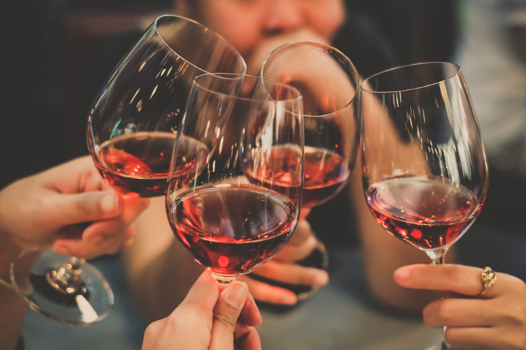 a group of friends toast glasses of wine at a Napa Valley winery