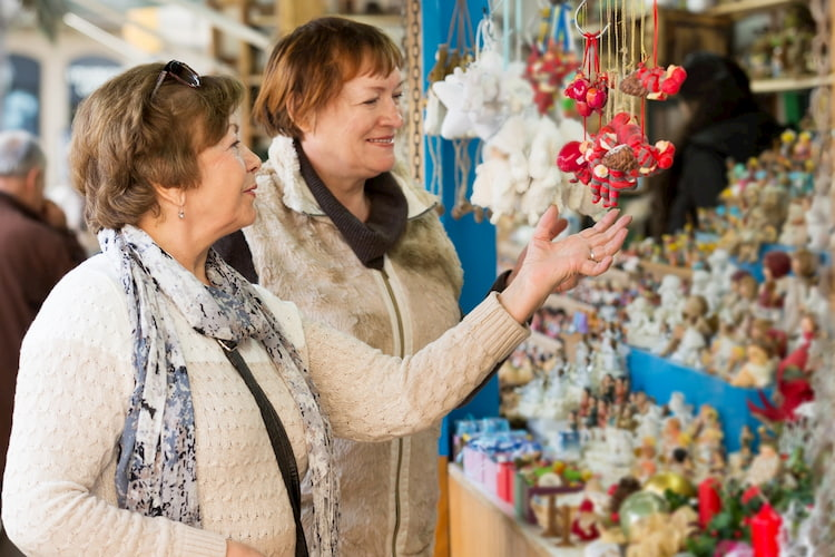 Two older women admire the crafts at a vendor booth at the Yellow Daisy Festival