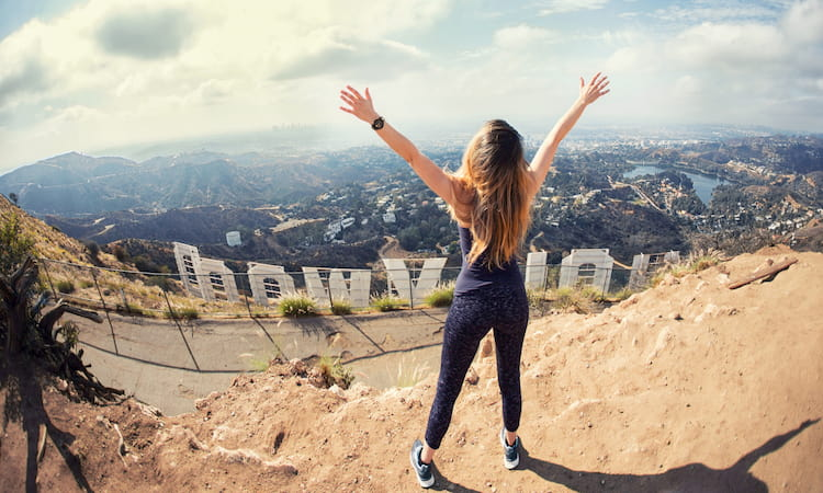 a woman hiker raises her arms to sky in triumph above the Hollywood sign
