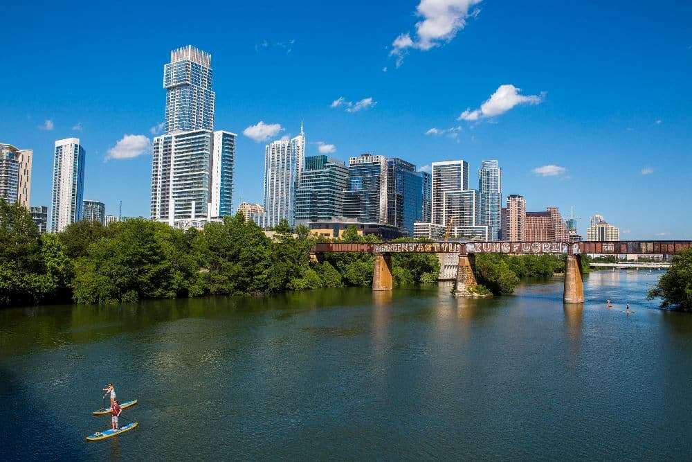 two paddleboarders on lady bird lake with austin in the background