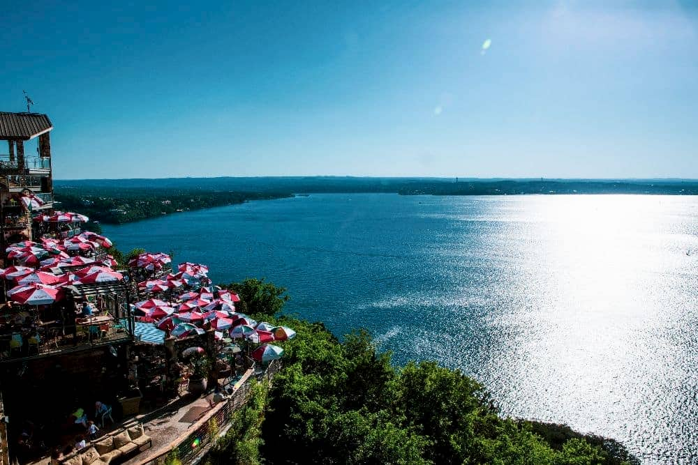 a view of a cliff looking over lake travis, with red and white umbrellas