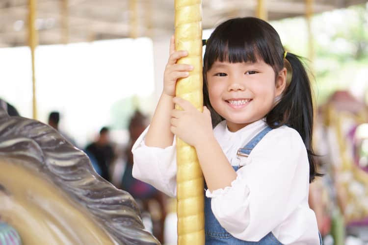 Little girl riding carousel horse