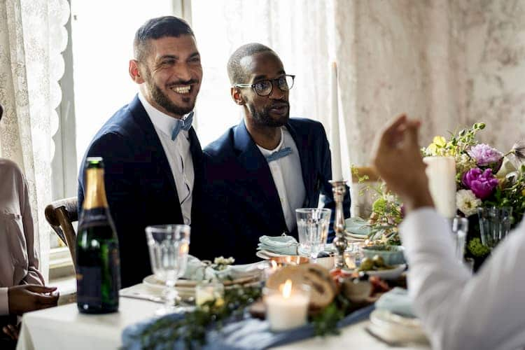 Two grooms at table at wedding reception
