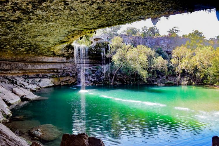 a waterfall and a blue pool of water at mckinney falls state park