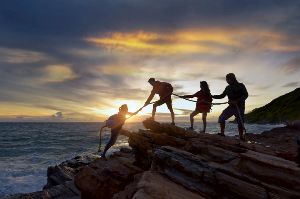 a group of friends help each other climb up the side of a rock, with a sunset in the background